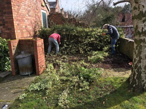 2 people clearing the overgrown shrubs in the garden at Richard House